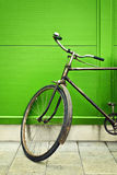 Old bicycle leaning on green wall Royalty Free Stock Image