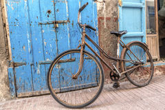 Old bicycle leaning on a weathered door Royalty Free Stock Images