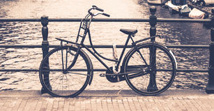 Old bicycle locked on a bridge over water canal, Amsterdam, Netherlands Royalty Free Stock Photos