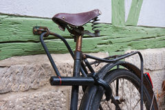 Old bicycle locked at a wall Stock Photography