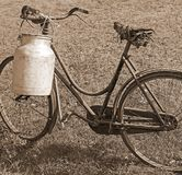 Old bicycle milkman with aluminum bin for transporting the milk. With sepia effect Royalty Free Stock Image