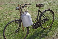 Very old bicycle of a milkman. Old bicycle milkman and the bin of aluminum for transporting the freshly milked milk Royalty Free Stock Photo