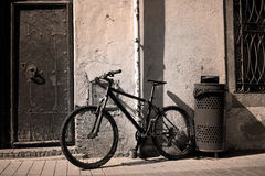 Old bicycle. Near the ancient walls and doors, sepia. Spain, Tossa de Mar stock photography