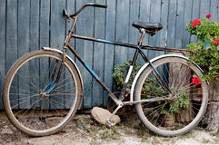 Old  bicycle near a blue wooden fence in village Royalty Free Stock Image
