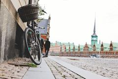 Old bicycle near wall in Copenhagen. A bike with  basket parked on a street in Copenhagen city Stock Photo