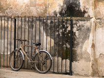 Old bicycle next to an old wall. Old bicycle standing alone next to an old wall Royalty Free Stock Image