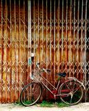 Old bicycle and old rustic metal door. Picture with copy space. Old and rustic concept royalty free stock photos