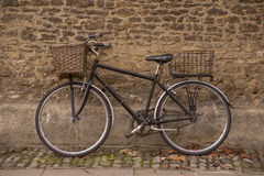 Old bicycle in Oxford. An old bicycle leant against the wall of Merton College in Oxford Stock Image