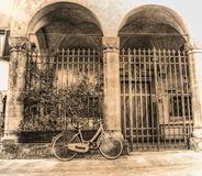 Old bicycle parked by a beautiful loggia in sepia tone Stock Photography