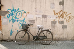 Old bicycle parking beside wall Stock Photo