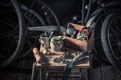 Old bicycle repair workshop with tools, wheels and tube. On dark background royalty free stock image