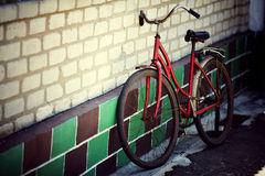 The old bicycle. Rusty from time costs near a wall royalty free stock photography