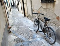 Old Bicycle, Side Street, Cefalu, Sicily. We came upon this old bike chained to the wall in a side street in Cefalu, Sicily. The cog and chain as well as the Royalty Free Stock Photo