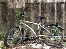 Old bicycle sitting beside cement wall Royalty Free Stock Photos