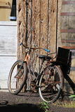 Old bicycle sitting in the sun. This old bicycle was leaning against this old building and I thought it captured a retro look Royalty Free Stock Images
