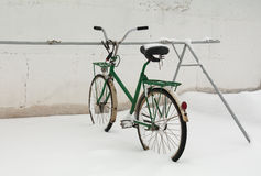 Old bicycle in snow. The old broken bicycle is brought by snow on parking stock image