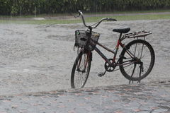 Old bicycle on the street in the pouring rain Stock Images