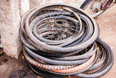Old bicycle tires and wheels. A pile of old bicycle tires sits abandoned near a wall Stock Image