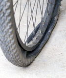 Old Bicycle wheel with flat tyre on road Royalty Free Stock Photography