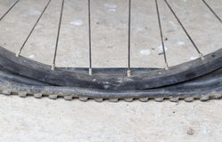 Old Bicycle wheel with flat tyre on road Royalty Free Stock Image