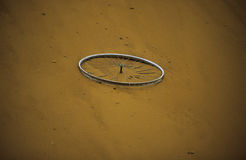Old Bicycle Wheel Rim, Fine Art. Old bicycle circle lying in a sandy hill of a gravel-pit royalty free stock photo