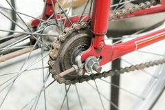 Old bicycle whell in red color with rusted chain royalty free stock photography