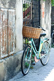 Old bicycle with wicker basket standing on the street Royalty Free Stock Images