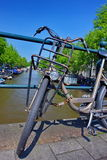 Old bicycles in Amsterdam. On the bridge Stock Photos