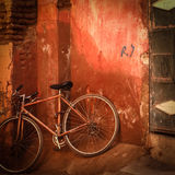 Old bicylce in front of grungy red wall Royalty Free Stock Photo