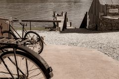 Old bicyle wheels in street in small town with group four youth in distance on jetty. CROMWELL, NEW ZEALAND - OCTOBER 21 2019; Old bicyle wheels in street in stock photo