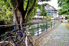 Old bicyles rested against a rail. Stretch of river in the city of Colmar, France with typical timbered houses in the distance Royalty Free Stock Photo