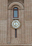 Old big clock on a brick wall. Under a window Stock Images