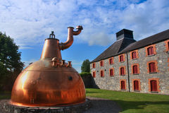 Old big copper whiskey distillery outdoor. Old big copper whiskey distillery on stone foundation outdoor stock image