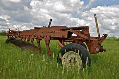 Old big plow parked in the grass Royalty Free Stock Image