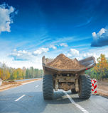 Old big tipper with ground on road in forest rear Royalty Free Stock Image