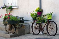 Old bicycle and cart with flowers leaning against house wall stock photos