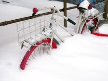 The old bike is covered with snow. Snow winter old bike stairs wood logs street cleaning town white holiday house object cold snow royalty free stock images