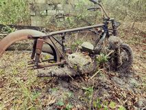Old bike found in the woods. Old antique motorcycle found in the woods stock photography
