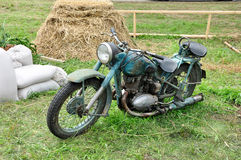 Old bike on the grass. Motorcycle on a background of bags, hay and fence Stock Photo