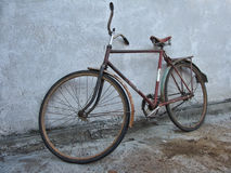 Old bike - grunge style. An image of old bicycle at the wall. Grunge style stock photography