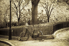 Old bike on a sidewalk in Montmartre. Old bike leaning against a fence in Montmartre (Paris, France). Retro sepia style Royalty Free Stock Image