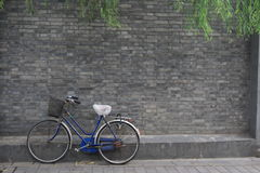 The old bike beside the wall Stock Photos