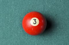 Old billiard ball number 3 red color on green billiard table, copy space royalty free stock photography