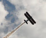 Old biplane. Vintage biplane performing an aerial stunt with smoke Stock Photos