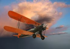 Old biplane in flight. Old World War I biplane in flight on evening sky background royalty free stock photography