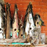 Old birdhouses in a row. A closeup of hand-made wooden birdhouses, covered in twigs and branches and left in a row next to a brick wall Royalty Free Stock Photos