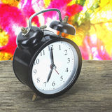 Old black alarm clock Cement wall background stock photo