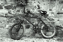 Old black bicycle on a rock wall in a smooth duotone scene Royalty Free Stock Photography