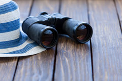 Old black binocular and hat Royalty Free Stock Image