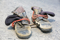 Old black boot and pole climber on road surface. Old boot and pole climber on road surface Royalty Free Stock Photos